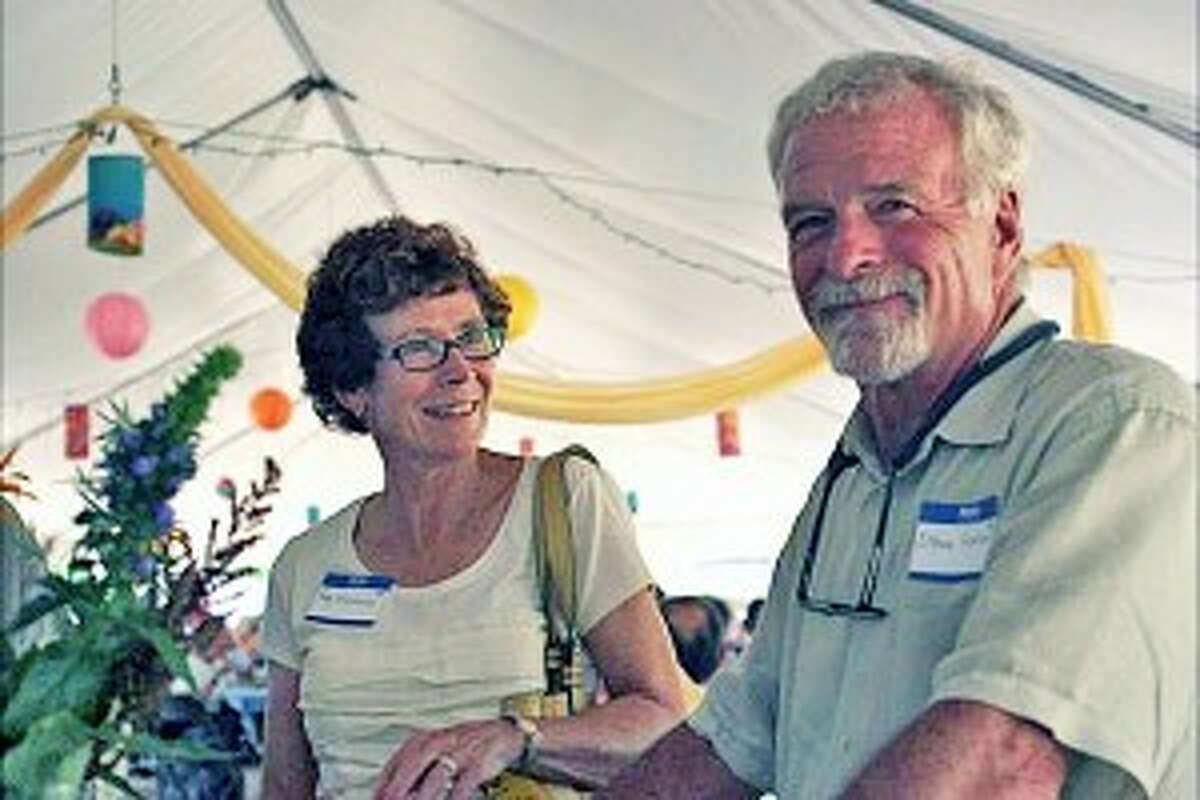 """Steve Wentworth and Peg Lawrenson in """"The Garden Party"""" tent at Grow Benzie, filled with mini lights, lanterns and fresh flowers."""