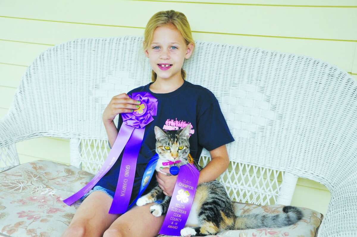 WINNING CAT: Sarah Hanmer and Lizzy the cat with their blue ribbons. (Courtesy photo)