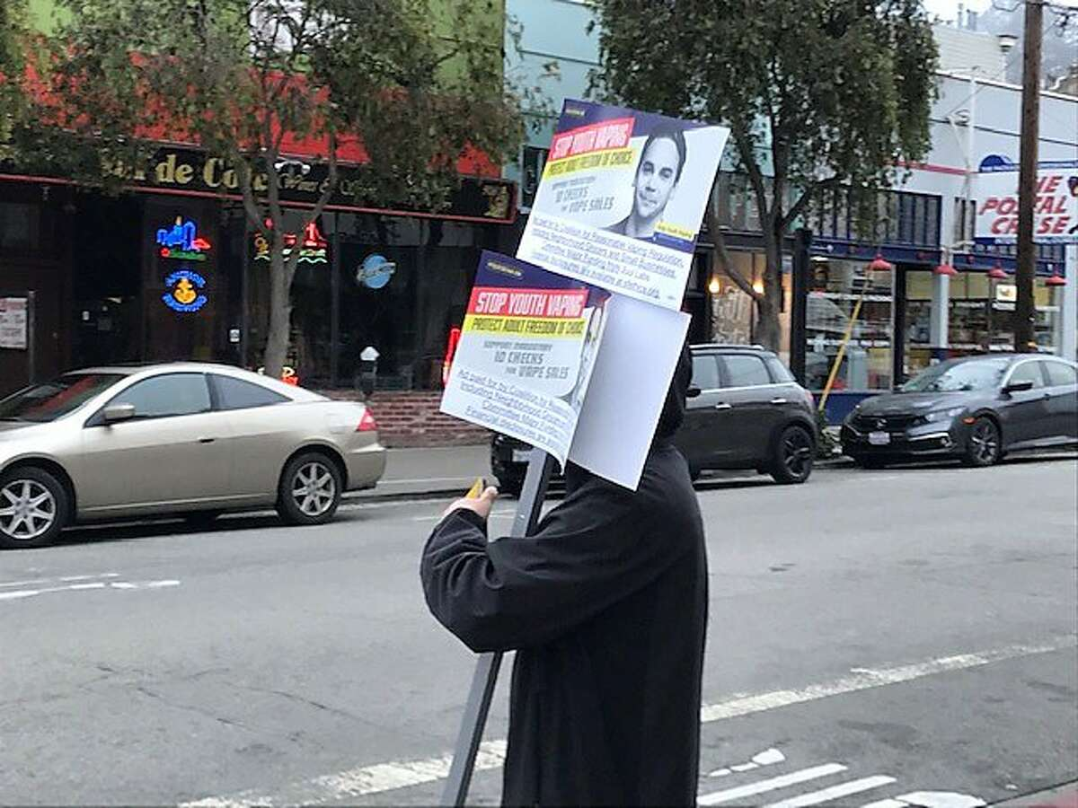A person holds campaign posters for the Juul-backed ballot measure by the Carl & Cole Muni stop in San Francisco on Wednesday, Aug. 7.