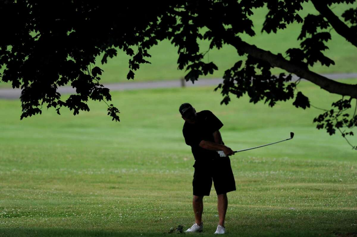 A golfer hits a shot from under a tree on the 2nd hole during the 2018 Stamford Amateur Championship at E. Gaynor Brennan Golf Course in Stamford, Conn. on Sunday, June 24, 2018. The city Golf Commission is one of many that has trouble filling seats.