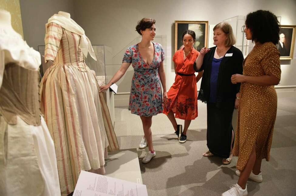 Hamilton cast members Hannah Cruz (Eliza Schuyler), left, Olivia Puckett (Peggy Schuyler) and Stephanie Umoh (Angelica Schuyler), right, are shown dresses by Curator Diane Shewchuk, second from right, during their visit to the Schuyler Sisters and Their Circle exhibit at the Albany Institute of History and Art on Friday, Aug. 16, 2019 in Albany, N.Y. (Lori Van Buren/Times Union)