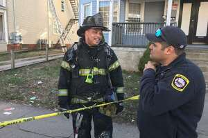 New Haven Fire Lt. Leon Brown, left, shown in this photo from a different incident, rushed to help shooting victims on Henry Street on August 12.