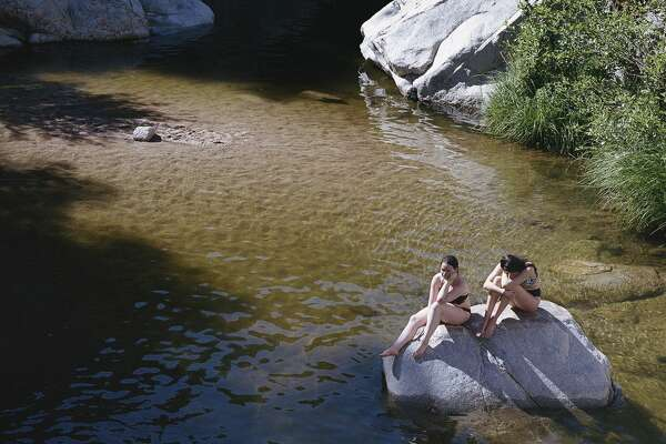 People swimming at Aztec Falls in San Bernardino County, Calif., on July 4th weekend in 2019. In California, water is precious. The state's hidden pools are yet another reason to treasure it. (Angal Field/The New York Times)