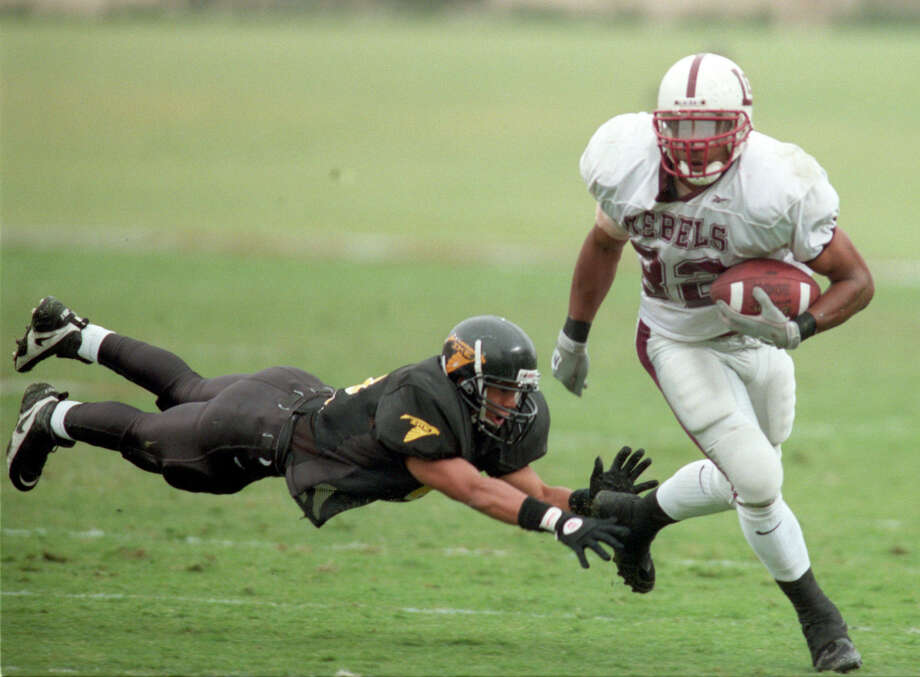 Lee's Cedric Benson, who rushed for 192 yards, turns the corner on Eisenhower's Marcus Smith in the 1999 Class 5A Division I title game. (Karen Warren/Houston Chronicle) Photo: Karen Warren,  Houston Chronicle