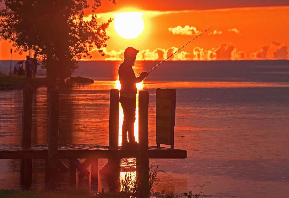 A young fisherman was recently spotted enjoying the sunset over Wild Fowl Bay, at Mud Creek Public Access, near Bay Port on a summer evening. Photo: Bill Diller/For The Tribune