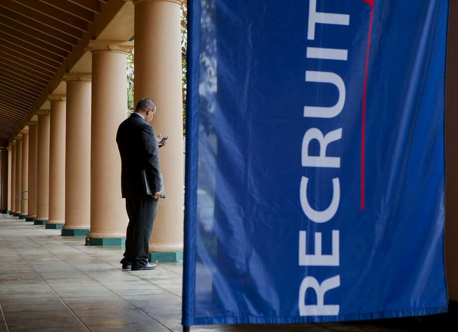 FILE - A job seeker checks his mobile phone outside the Recruit Military veteran job fair in San Diego, California, U.S., on Thursday, Feb. 27, 2014. The California Employment Development Department released figures on the state unemployment rate. Photo: Sam Hodgson, Bloomberg