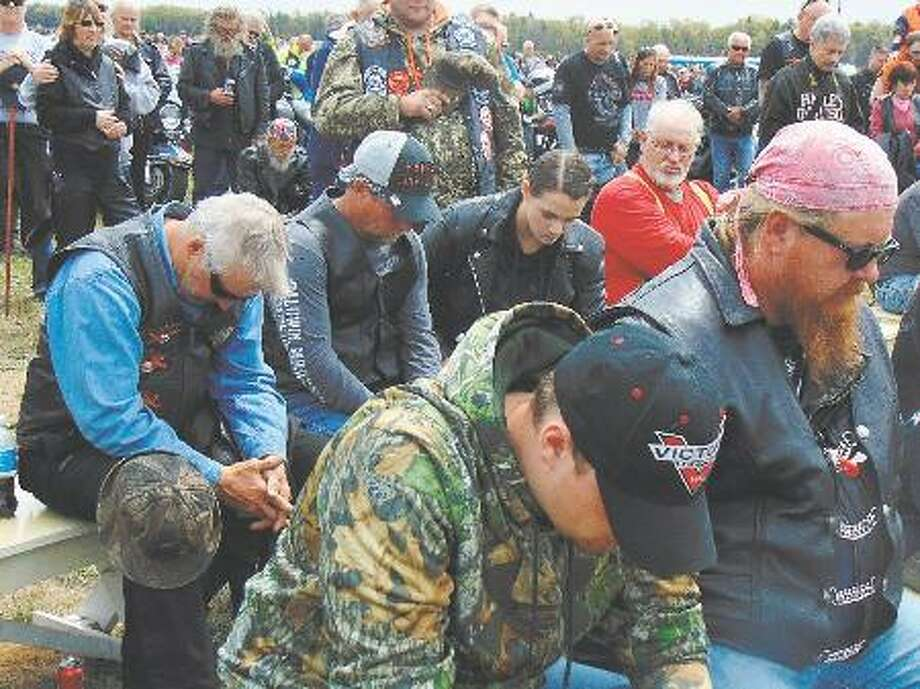 Bikers bowed their heads in prayer during the blessing.