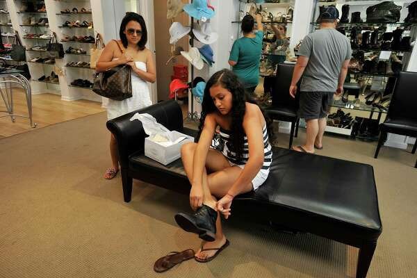 A New Rochelle, N.Y. girl tries on shoes at Shoes 'N' More in Greenwich, Conn., in August 2014 during Connecticut's annual sales tax holiday.