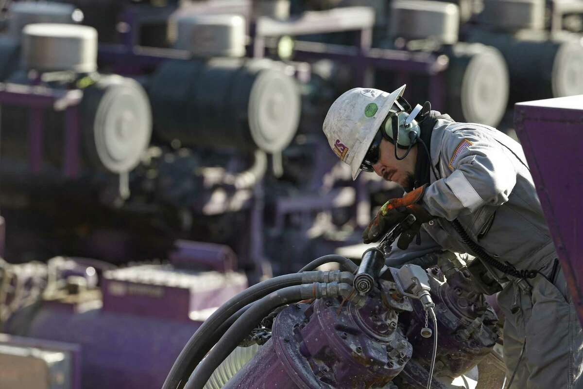 A worker oils a pump during a hydraulic fracturing operation at an Encana Corp. well pad near Mead, Colo. Encana is preparing for a large round of horizontal drilling in the Permian Basin.