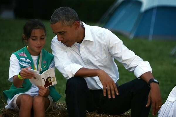 WASHINGTON, DC - JUNE 30: Daphnye Shell (L) of Peggs, Oklahoma, shares her song book with U.S. President Barack Obama (R) during a campfire songs session at the first-ever White House Campout June 30, 2015 at South Lawn of the White House in Washington, DC.