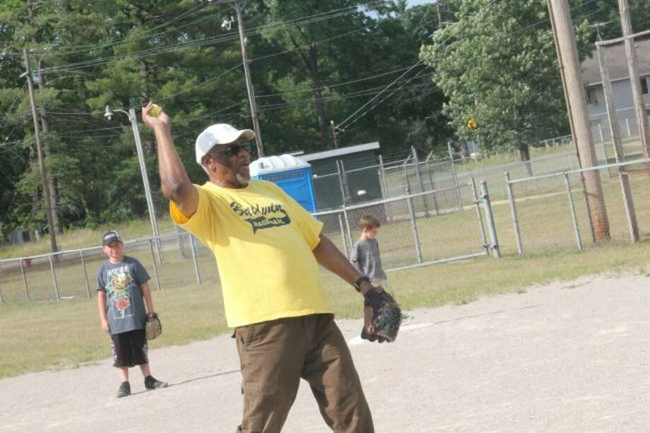 Lee Moore delivers a pitch at a youth league practice.