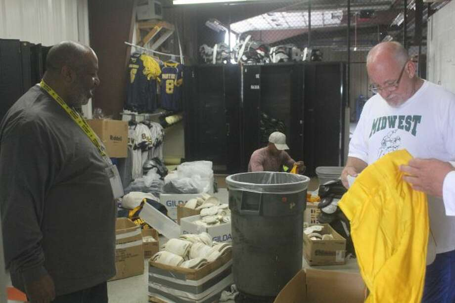 Baldwin football coaches sort through the equipment.