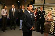 """FILE - This 2007 file image originally provided by NBC Universal shows a scene from NBC's """"The Office,"""" showing Steve Carell, center, as Michael Scott. Inept branch manager Michael Scott departs """"The Office"""" on Thursday's episode of the popular NBC comedy, taking series star Steve Carell with him. Also pictured are cast members, from left, Oscar Nu�ez, Brian Baumgartner, Leslie David Baker, Ed Helms, Mindy Kaling, Phyllis Smith, Creed Bratton and Angela Kinsey. (AP Photo/NBC, Justin Lubin)"""