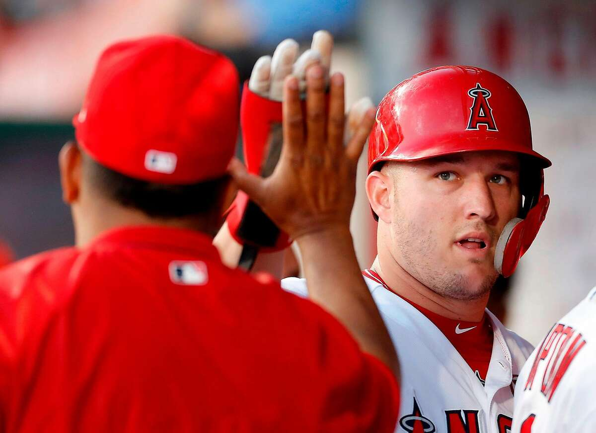 The Los Angeles Angels' Mike Trout is congratulated in the dugout after scoring a run against the Pittsburgh Pirates in the first inning on Tuesday, Aug. 13, 2019, at Angel Stadium in Anaheim, Calif. (Luis Sinco/Los Angeles Times/TNS)