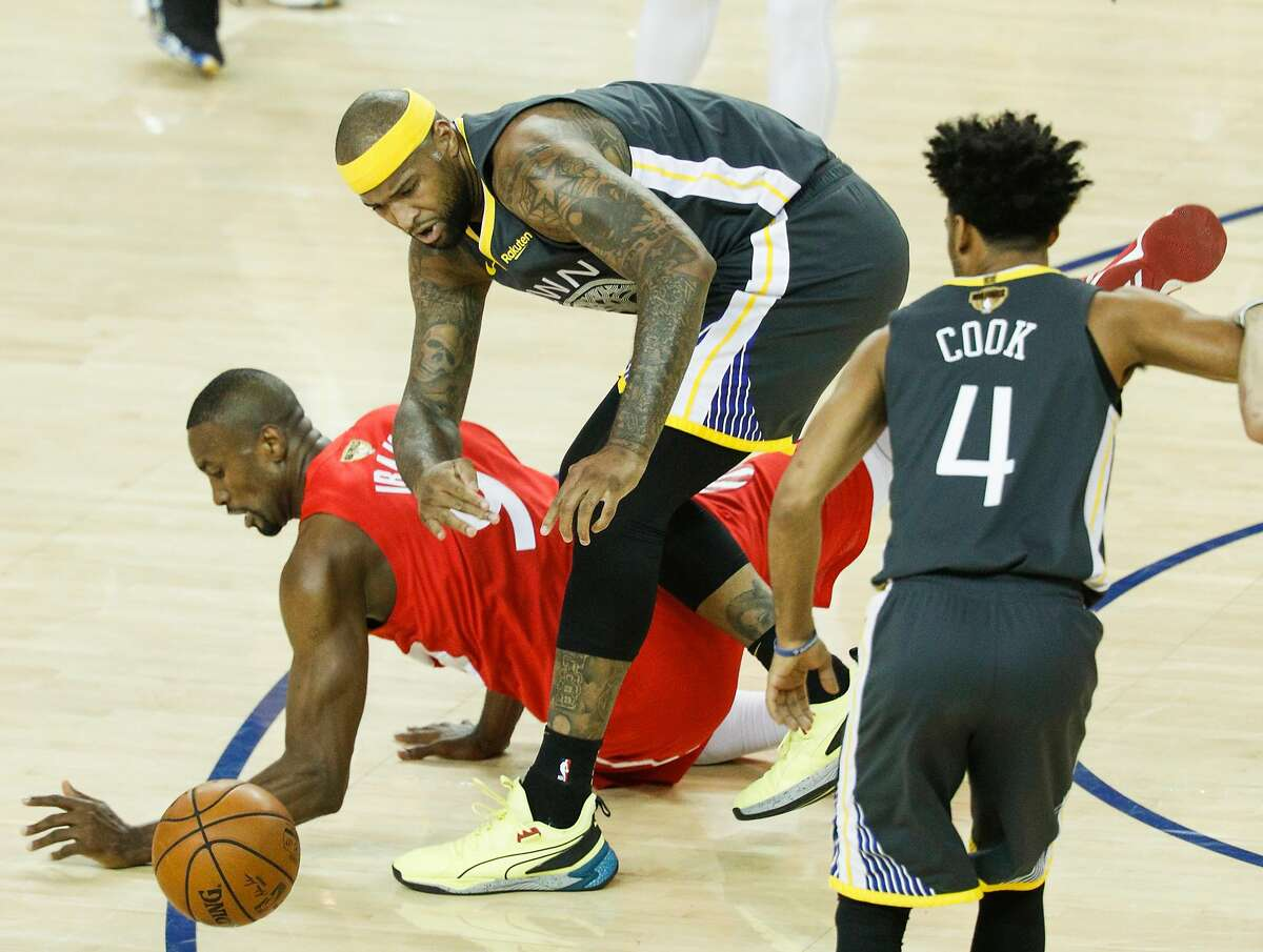 Golden State Warriors' DeMarcus Cousins and Toronto Raptors' Serge Ibaka chase a loose ball in the second quarter during game 6 of the NBA Finals between the Golden State Warriors and the Toronto Raptors at Oracle Arena on Thursday, June 13, 2019 in Oakland, Calif.