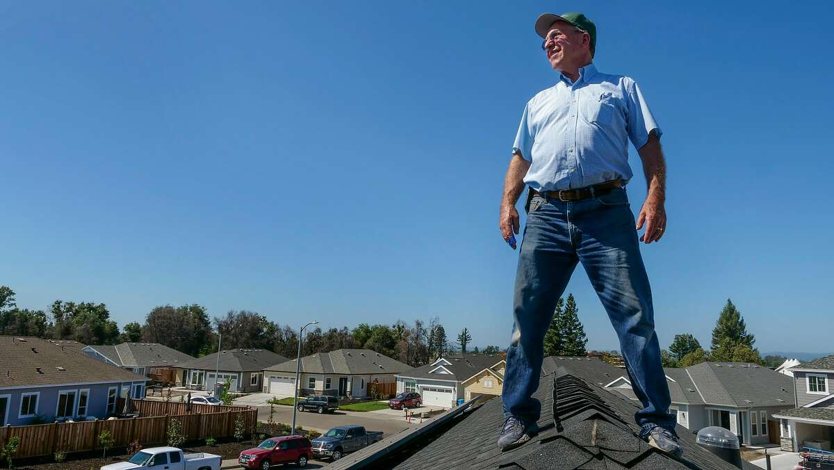 Bob Cipolla stands on the roof with the solar panels at his new home which is under construction, Friday August 16, 2019, in Santa Rosa, Ca. HIs home is all-electric with the help of Sonoma Clean Power's Advanced Energy Republic program that helps homeowners affected by October 2017 fires republic energy efficient homes. The electricity that is generated from his home will feed the grind to help his neighbors with their power. � I use to think off the grid was in the woods but it�s right here,� said Cipolla.