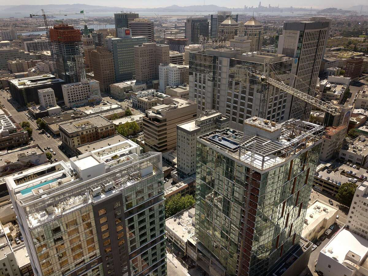 The construction site of a 20-story residential building going up on the 1700 block of Webster Street, lower left, is visible amidst several finished and unfinished construction projects in Oakland Calif., on Wednesday, July 17, 2019. Oakland�s downtown has long been revered as hip, electric and historic. Five years ago, the area underwent a transformation minority-owned nail salons shuttered and were instead replaced by hipster bike shops. Now, stores and other businesses are facing a similar transformation as cranes dot the skyline and 20-story buildings go up. One downtown block, near 17th and Webster, is a microcosm of the change that�s coming once again to downtown Oakland. There are three big development projects currently under construction on that block - two of which will have 20-story towers.
