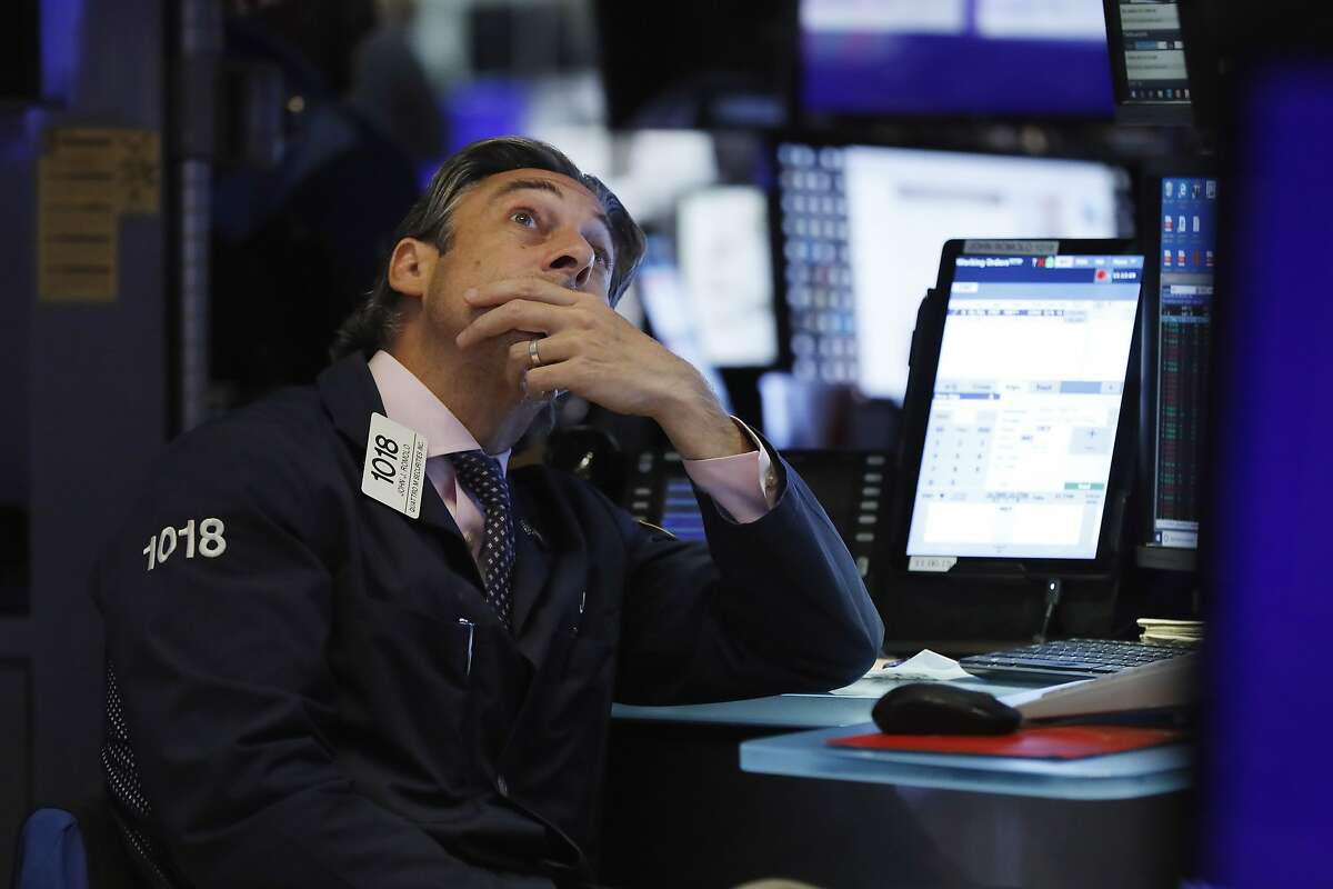 Trader John Romolo works on the floor of the New York Stock Exchange, Wednesday, Aug. 7, 2019. U.S. stocks fell broadly in midday trading Wednesday as central banks around the world cut interest rates and increased fears that global growth is being crimped by the U.S.-China trade war. (AP Photo/Richard Drew)