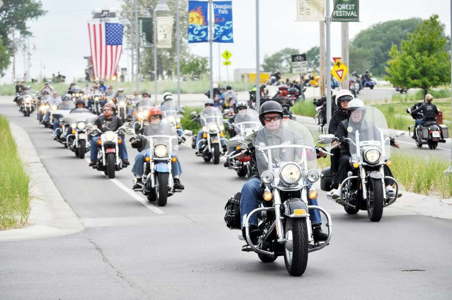 A PACK OF RIDERS: Some of the members of the AMVETS Riders Chapter 1988 in Baldwin are shown together in Manistee. The approximately 20 motorcycle riders joined others to escort the Michigan Vietnam Veterans Traveling Memorial through Manistee on Friday. (Star photos/Eric Sagonowsky)