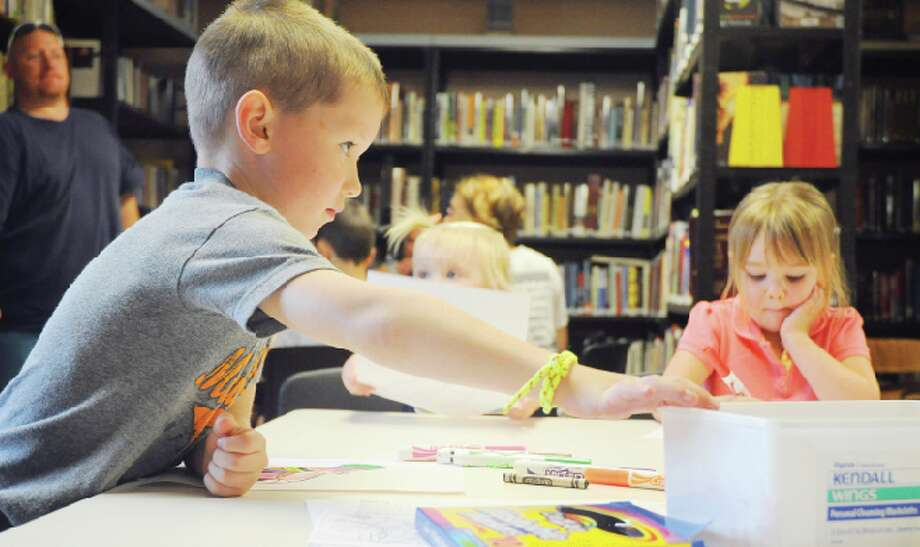 """SUMMER FUN: Three young children color pictures of worms on Wednesday at the Chase Township Public Library. The activity was part of the library's summer reading program theme of """"Dig into Reading."""" (Star photo/Kyle Leppek)"""