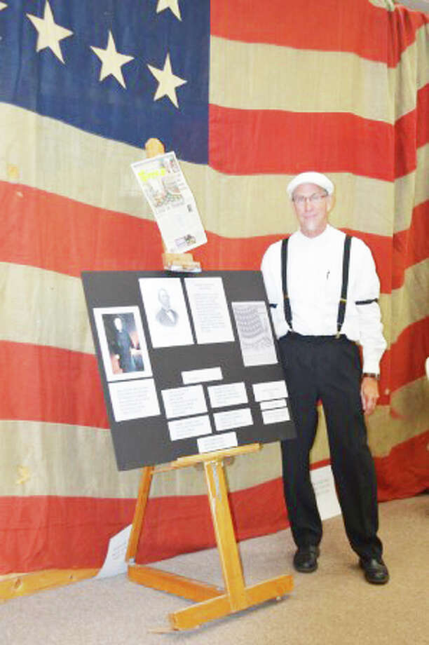 DRESSED THE PART: Lake County Historical Society President Bruce Micinski, dressed in vintage clothing, stands in front of an American flag from the 1870s during the annual Lake County History Day. (Courtesy photos)