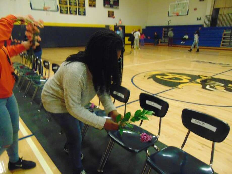 Kendra Washington places flowers on chairs representing the students who were killed in Parkland, Fla.