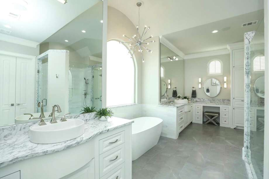 This remodeled master bath features tube sconce lights.