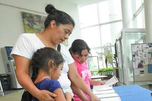 Albertina Chibalan-Pastor of Stamford, hugs her daughter Ariana as she looks at literature with Maria Olivia while signing up for a free or reduced lunch program on Aug. 7, 2019 at the Stamford Government Center in Stamford, Connecticut. The program is offered to students attending Stamford Public Schools.