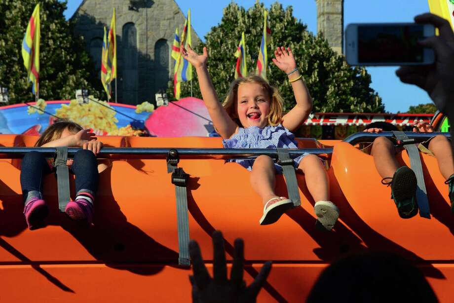 Amelia MacKinnon, 4, of Fairfield, waves to her mom as she rides the Happy Swing during Our Lady of Assumption Church's 24th annual SeptemberFest fair on the church grounds in Fairfield, in 2017. The annual family fair returns Sept. 13-15. Photo: Christian Abraham / Hearst Connecticut Media File Photo / Connecticut Post