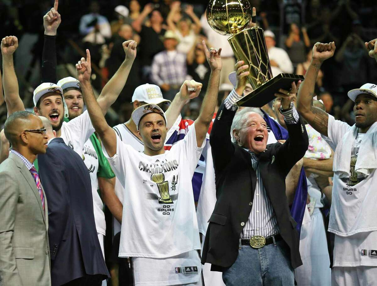 The Spurs' Marco Belinelli, Tony Parker, owner Peter Holt, Kawhi Leonard and others celebrate after defeating the Miami Heat in Game 5 to win the 2014 NBA Finals on June 15, 2014 at the AT&T Center. The Spurs won 104-87.