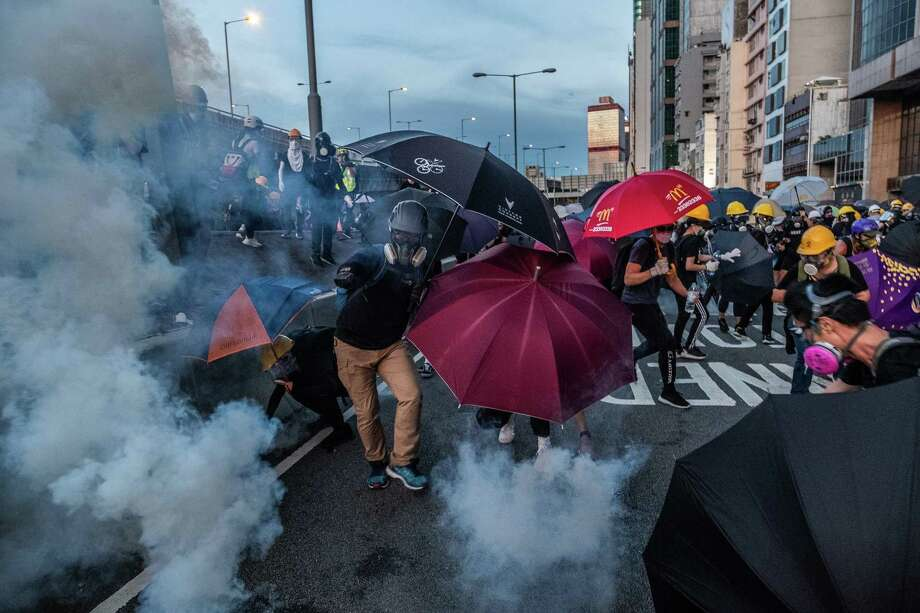 Protesters use umbrellas to shield themselves from tear gas fired by riot police during a clash in Hong Kong in July. Photo: Lam Yik Fei /New York Times / NYTNS
