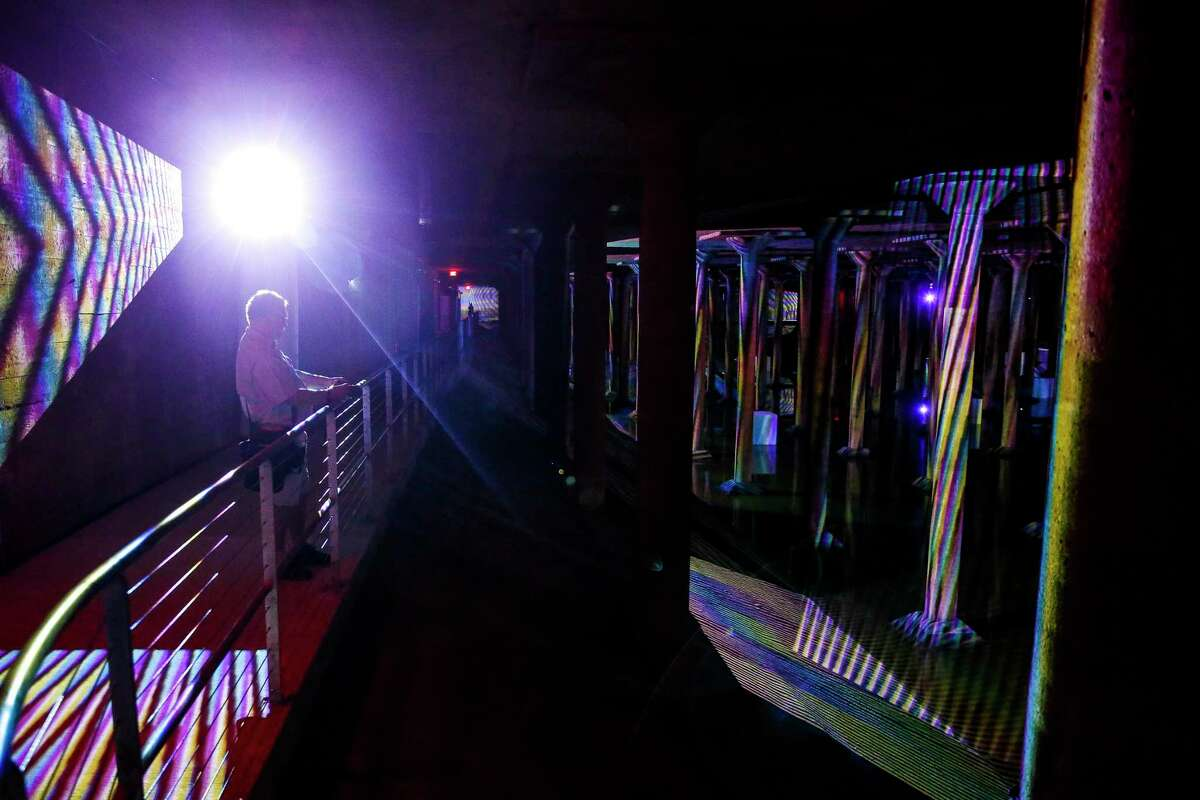"""Visitors look at Carlos Cruz-Diez's site specific """"Spacial Chromointerference"""" at the Buffalo Bayou Park Cistern in 2018. (Michael Ciaglo / Houston Chronicle)"""