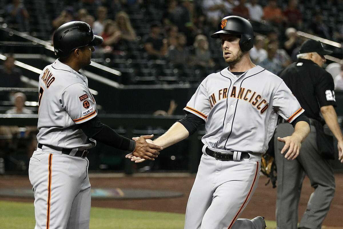 San Francisco Giants' Austin Slater is greeted by Donovan Solano after they scored against the Arizona Diamondbacks during the first inning of a baseball game Thursday, Aug. 15, 2019, in Phoenix. (AP Photo/Darryl Webb)
