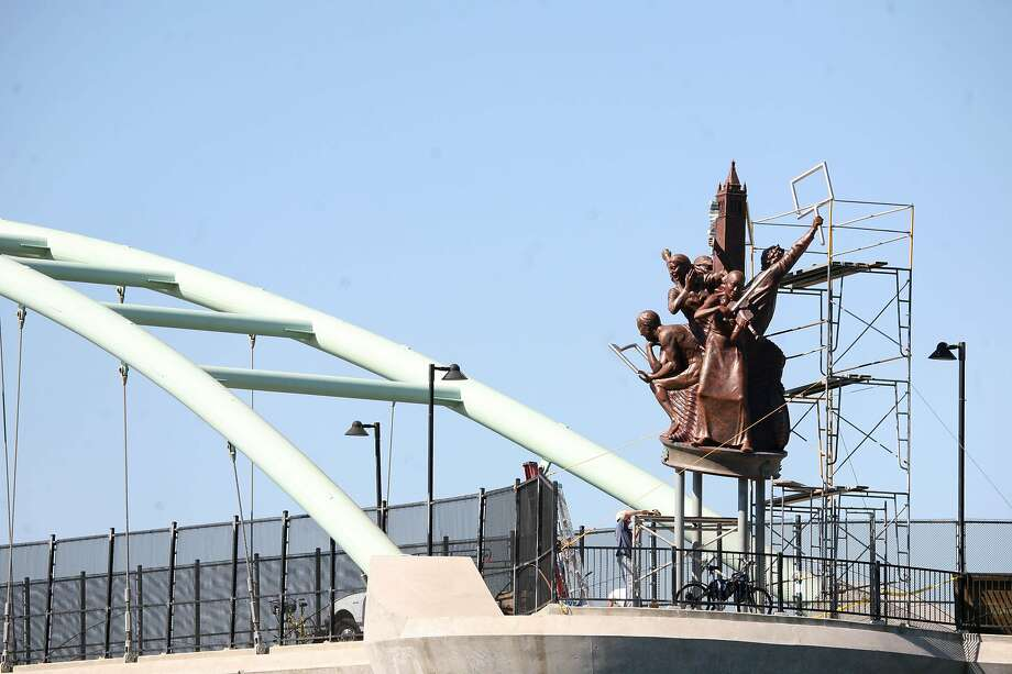 "FILE - Emeryville artist Scott Donahue's 30-foot sculpture, ""Berkeley Big People,"" undergoing installation on the pedestrian bridge over I-80 on Oct. 15, 2008 in Berkeley. Berkeley's Civic Arts Commission is considering removing the statutes. Photo: Lea Suzuki, The Chronicle"