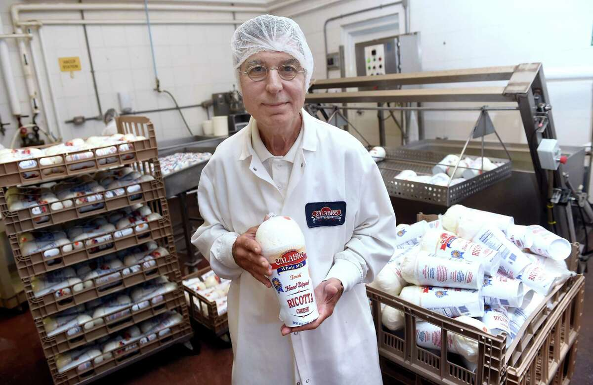 Frank Angeloni, president of the Calabro Cheese Corporation, holds the company's prize-winning hand-dipped ricotta cheese at the factory in East Haven.