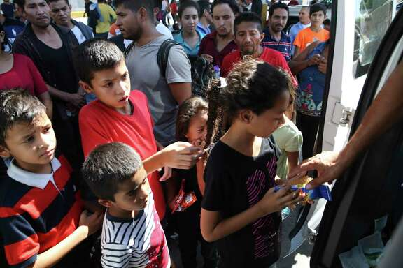 Migrant children line up for treats from Baptist volunteers at the Mexican immigration offices on International Bridge No. 1 in Nuevo Laredo, Mexico, Wednesday, Aug. 14, 2019. The migrants crossed into the U.S. seeking asylum but were sent back to Mexico under the Migrant Protection Protocols. The large group of migrants remained by the offices for security reasons. They feared kidnappings by cartels operating in the city. They said they would be provided with transportation back to the southern Mexican border but some were waiting for three days. Most wanted to return to their home country.