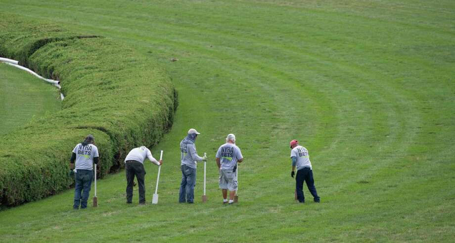 The grounds crew walk the Mellon Turf Course at the Saratoga Race Course and they refill the divots from a previous race to keep the course in good condition Friday Aug. 16, 2019  in Saratoga Springs, N.Y. Photo Special to the Times Union by Skip Dickstein