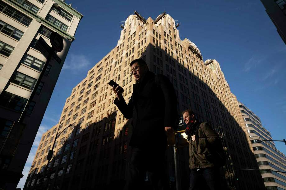 FILE - In this Dec. 17, 2018, file photo people walk by a building in New York. You carry your smartphone everywhere. But the way you use it could leave you vulnerable to specific forms of identity theft, including robocall scams and hackers looking to hijack your phone number. (AP Photo/Mark Lennihan, File) Photo: Mark Lennihan / Copyright 2018 The Associated Press. All rights reserved.