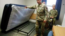 Chief Master Sgt. Christopher Lantagne lifts bed to show mold on carpet beneath it under the bed during a media tour Aug. 1. In background is Brig. Gen. Laura Lenderman.