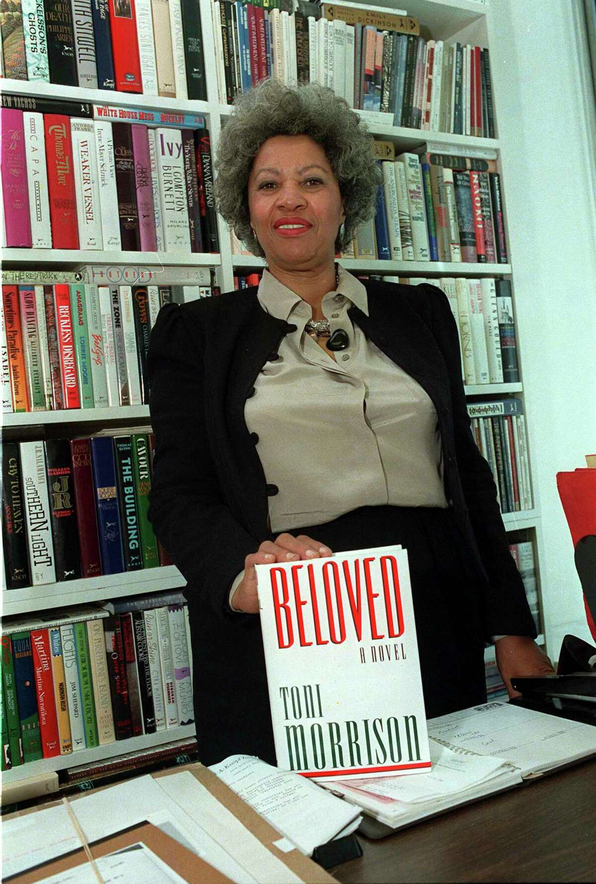 """In this September 1987 file photo, author Toni Morrison poses with a copy of her book """"Beloved"""" in New York."""