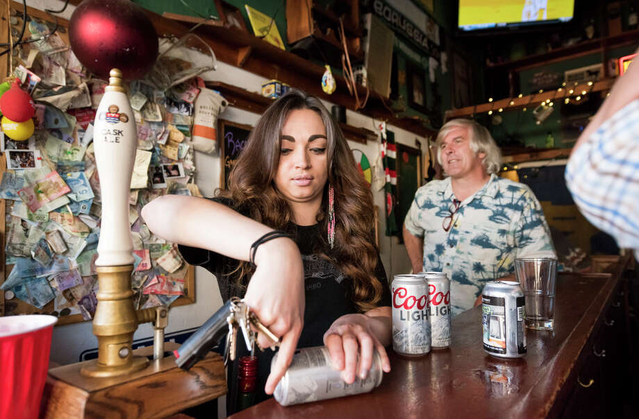 "Cassandra Harvell prepares a Coors Light to ""shotgun"". Photo: Blair Heagerty / SFGate"