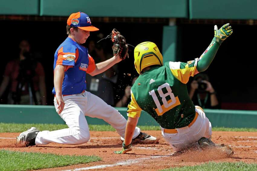 Coon Rapids, Minnesota's Tyler Phillips (18) scores ahead of the tag by Bowling Green, Kentucky's Grayson Newman during the second inning of a baseball game at the Little League World Series tournament in South Williamsport, Pa., Friday, Aug. 16, 2019. (AP Photo/Gene J. Puskar)
