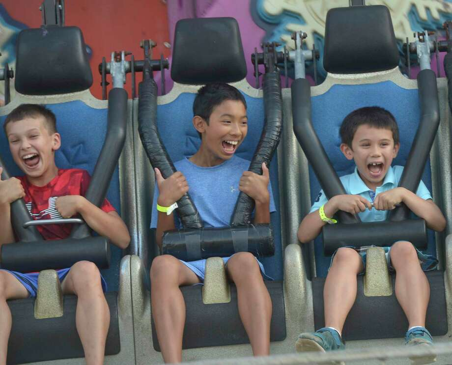 Isaac St George, of Newtown, left, and brothers Sam, 12, and Jake Papsin, 8, of Brookfield, enjoy a ride on the Avalance during the 68th Bridgewater Country Fair on Friday, August 16, 2019, in Bridgewater. At right, James Galbraith, of New Milford, a 3rd generation fair worker, places top rounds on a spike to be cooked and served as roast beef sandwiches. Photo: H John Voorhees III / Staff Photographer / The News-Times