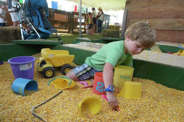Marcello Lazzaro, 3, of New Milford, plays in a corn box, which is like a sand box but uses kernals of corn instead, at the 68th Bridgewater Country Fair on Friday, August 16, 2019, in Bridgewater, Conn. Bill Morgan, of Bethel, makes an adjustment to the carb of a sandwich 1 cylinder, 3ho, engine from the 1920's