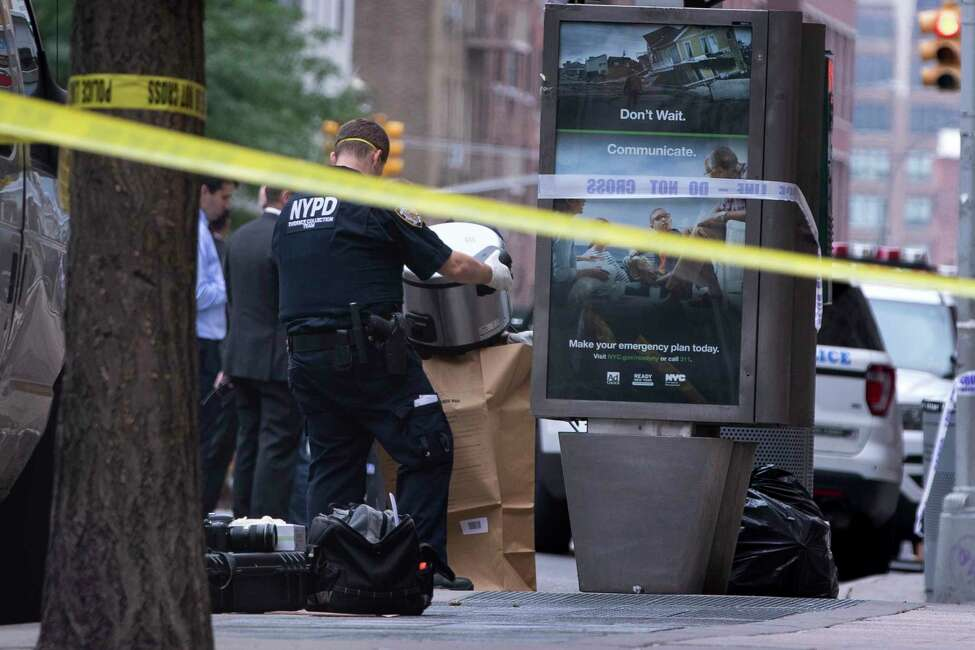 An investigator bags a suspicious package as evidence after it was thought to be an explosive device in Manhattan's Chelsea neighborhood Friday, Aug. 16, 2019, in New York. The scare happened about two hours after two abandoned objects that looked like pressure cookers prompted an evacuation of a major transit hub in lower Manhattan. The police bomb squad later determined they were not explosives. (AP Photo/Kevin Hagen).