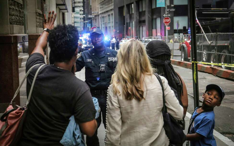 An NYPD anti-terror officer prevents pedestrians to pass, as police seal off area in the financial district around the the Fulton Street subway hub to investigate a suspicious item, Friday Aug. 16, 2019, in New York. Two abandoned objects that appeared to be pressure cookers prompted an evacuation of a major lower Manhattan subway station during the morning commute Friday before police determined they were not explosives, and authorities were investigating whether they were deliberately positioned to spark fear. (AP Photo/Bebeto Matthews)