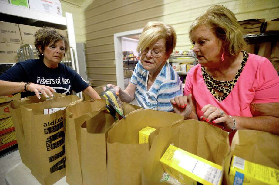 From left, Vanessa Kilmer, Pat Zatopek and Lavonda Charleston fill bags with groceries as volunteers with the Fishers of Men ministry, a non-profit organization that helps provide food and other items to those in need, work at their warehouse space behind Turning Point Church in Vidor Tuesday night. Photo taken Tuesday, August 13, 2019 Kim Brent/The Enterprise Photo: Kim Brent / The Enterprise / BEN