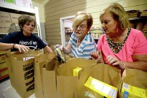 From left, Vanessa Kilmer, Pat Zatopek and Lavonda Charleston fill bags with groceries as volunteers with the Fishers of Men ministry, a non-profit organization that helps provide food and other items to those in need, work at their warehouse space behind Turning Point Church in Vidor Tuesday night. Photo taken Tuesday, August 13, 2019 Kim Brent/The Enterprise