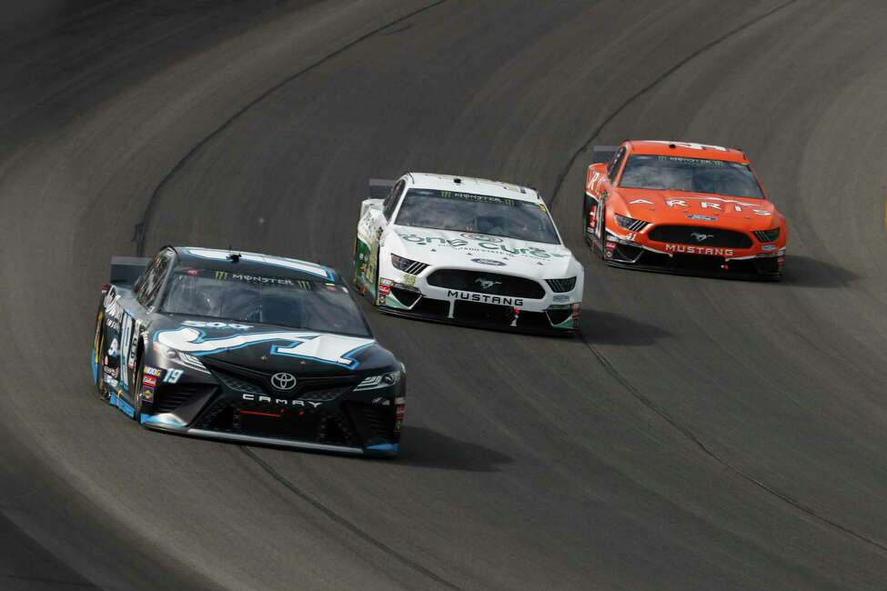 Martin Truex Jr. (17), from left, Clint Bowyer (14) and Daniel Suarez (41) race out of turn one during a NASCAR Cup Series auto race at Michigan International Speedway in Brooklyn, Mich., Sunday, Aug. 11, 2019. (AP Photo/Paul Sancya)