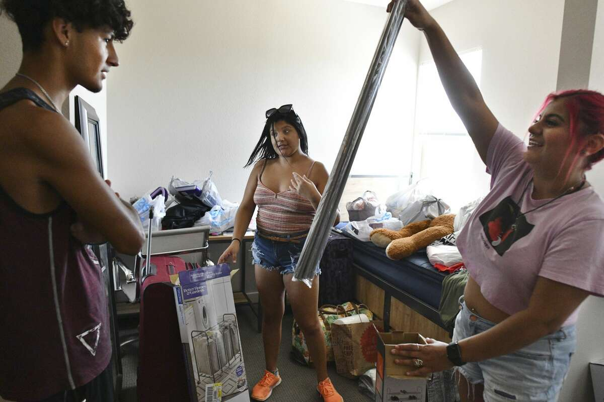 Miranda Pacheco, middle, a freshman moving into Esperanza Hall at Texas A&M University-San Antonio, gets help from her boyfriend, Alejandro Nava, left, and sister, Minerva, right, on Friday, Aug. 16, 2019. Almost 400 students will live in the three-year-old dorm, which is at capacity.